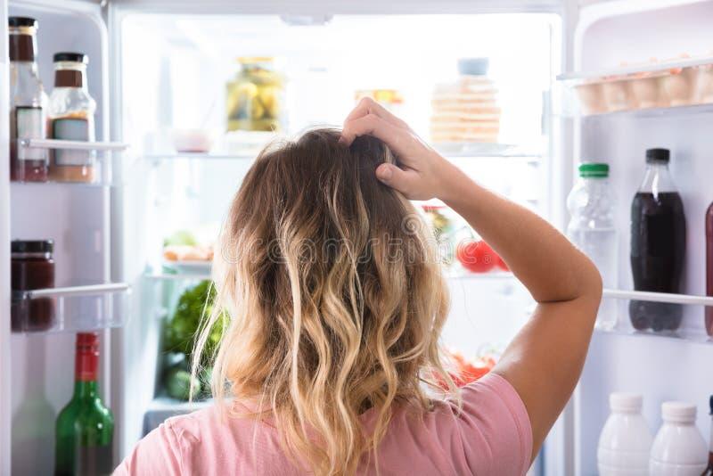 Förvirrad kvinna som ser i öppet kylskåp arkivbilder