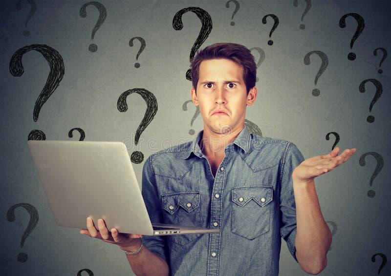 Förvirrad man med bärbara datorn många frågor och inget svar royaltyfri bild