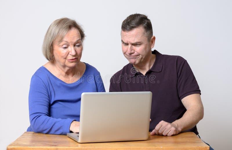 Förvirrad man och lekvinna som använder bärbara datorn arkivfoton