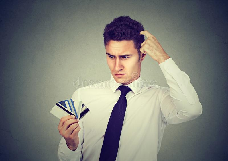 Förvirrad man som ser många osäkra kreditkortar vilket för att välja arkivfoto