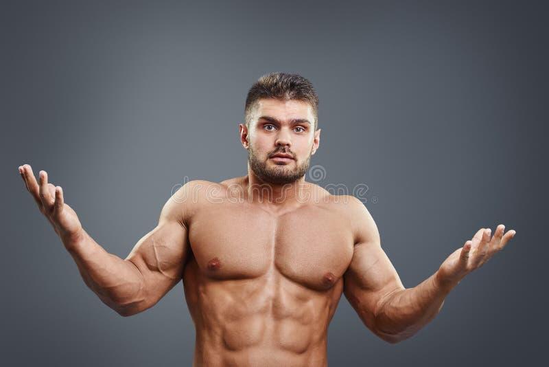 Förvirrad muskulös shirtless ung man som är osäker eller fotografering för bildbyråer