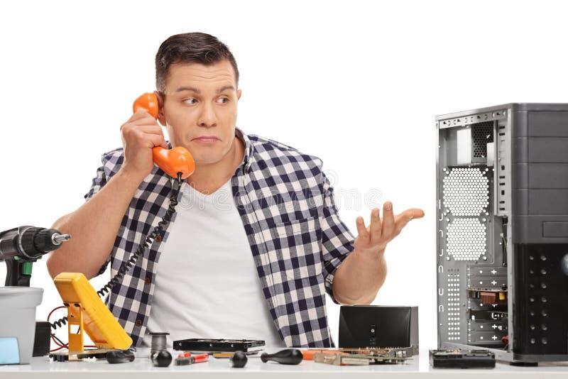 Förvirrad PCtekniker som talar på telefonen arkivfoto