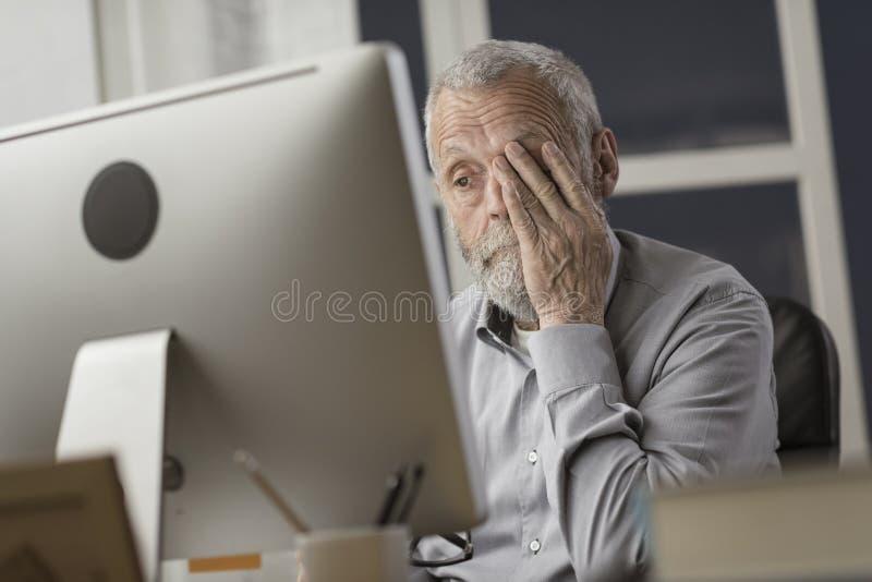 Förvirrad pensionär som använder en dator royaltyfri fotografi