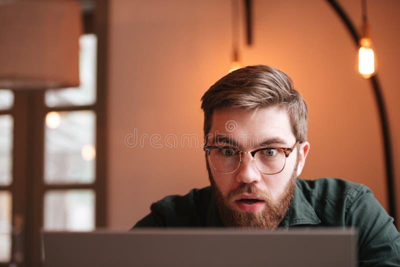 Förvirrad skäggig ung man som använder bärbar datordatoren royaltyfri foto