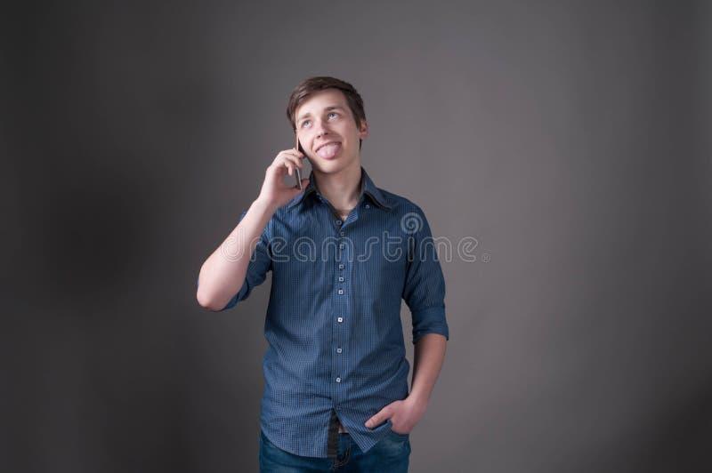 Förvirrad stilig ung man i blå skjorta med att klibba ut tungan som talar på smartphonen fotografering för bildbyråer