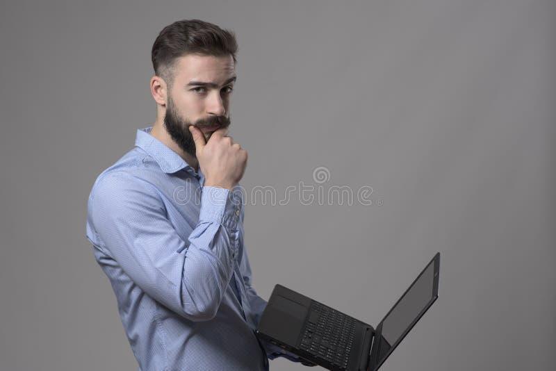 Förvirrad ung affärsman som använder det rörande skägget för bärbar datordator och ser kameran royaltyfri bild