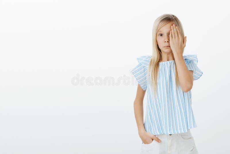Förvirrad ung flicka som känner sig konstig se något som är skamlig Studion sköt av förtjusande gullig dotter med ganska hår royaltyfri foto