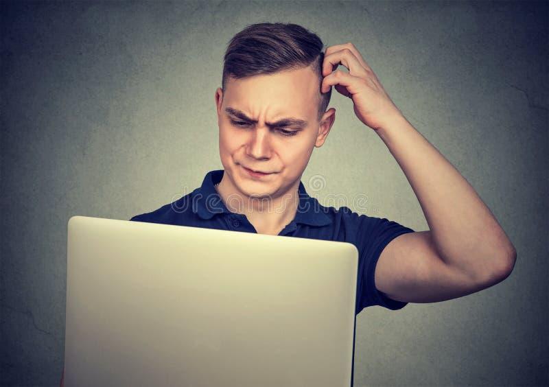 Förvirrad ung man med bärbara datorn royaltyfri bild