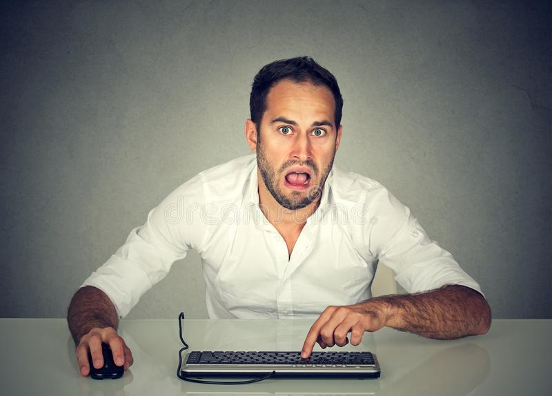 Förvirrad uppriven man som arbetar på datoren royaltyfri foto