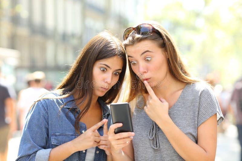 Förvirrade flickor som utomhus kontrollerar den smarta telefonen royaltyfria foton