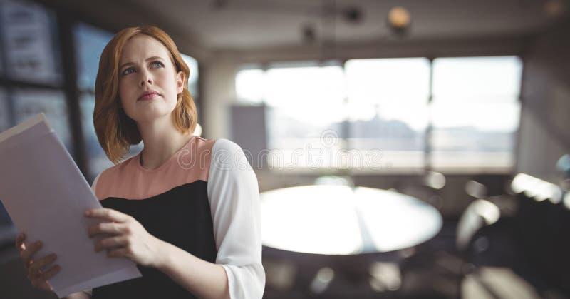 Förvirrade hållande mappar för affärskvinna mot kontorsbakgrund royaltyfria foton