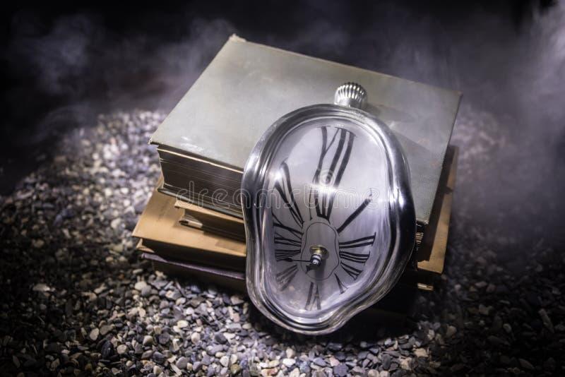 Förvriden mjuk smältande klocka på en träbänk, ståndaktigheten av minnet av Salvador Dali royaltyfria foton