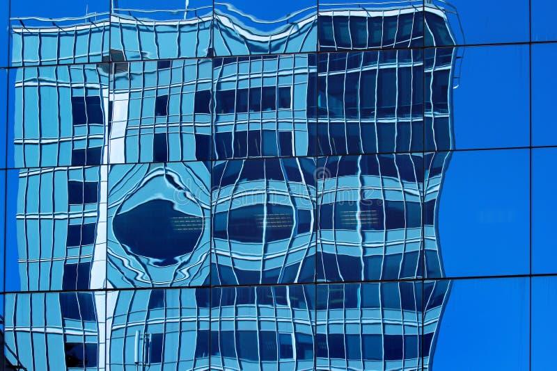 Förvriden reflexion i en vägg av glass kontorsbyggnad arkivbild