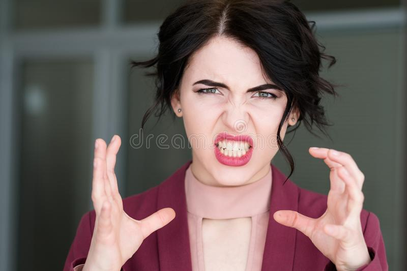 A fúria da raiva da cara da emoção estrangula a mulher que descobre os dentes imagem de stock royalty free