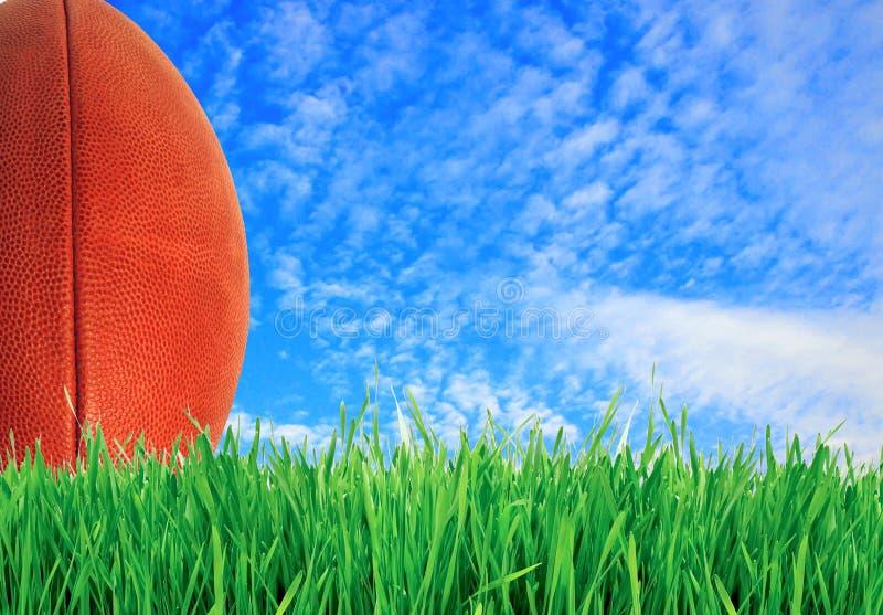 Fútbol americano (bola de rugbi) en hierba verde sobre el cielo azul fotografía de archivo libre de regalías