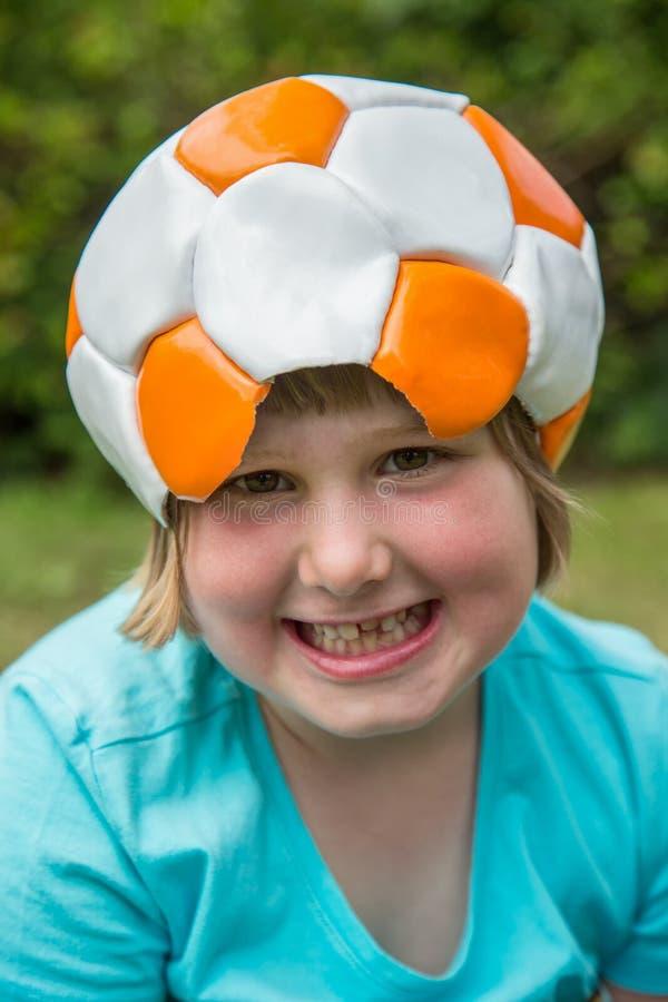 Fútbol de cuero que lleva de la chica joven en la cabeza fotografía de archivo libre de regalías