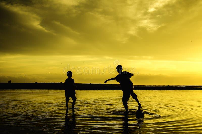 Fútbol de la playa del juego de los muchachos durante salida del sol de la puesta del sol foto de archivo