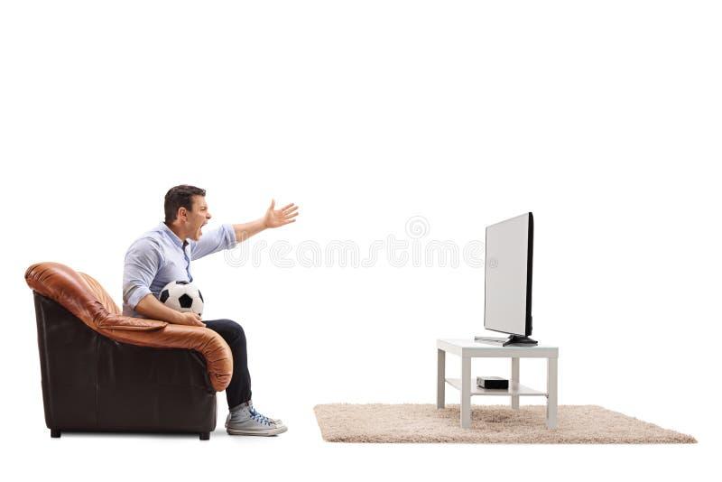 Fútbol de observación del hombre enojado en la TV y el grito foto de archivo