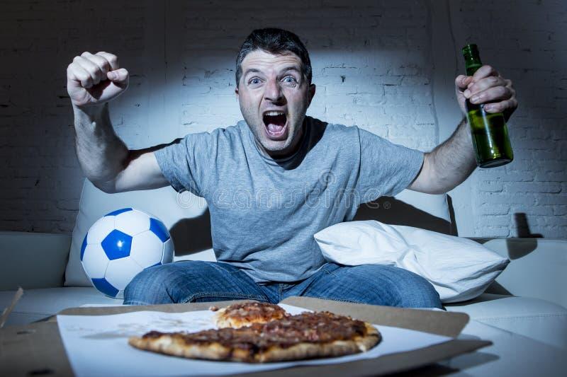 Fútbol de observación loco fanático de la televisión del fanático del fútbol que grita meta que anota de celebración feliz fotografía de archivo libre de regalías