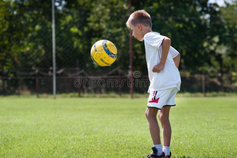 Fútbol de retroceso con el pie del muchacho fotos de archivo libres de regalías