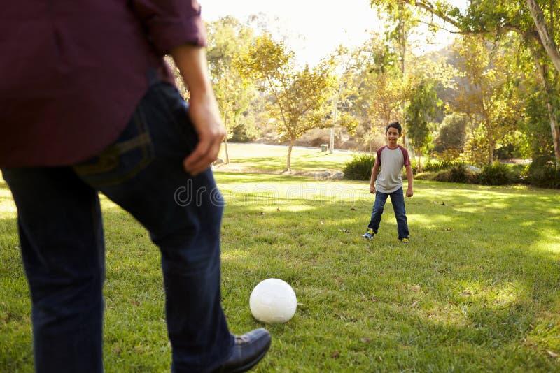 Fútbol de retroceso con el pie del papá al hijo de siete años en un parque, cosecha foto de archivo libre de regalías