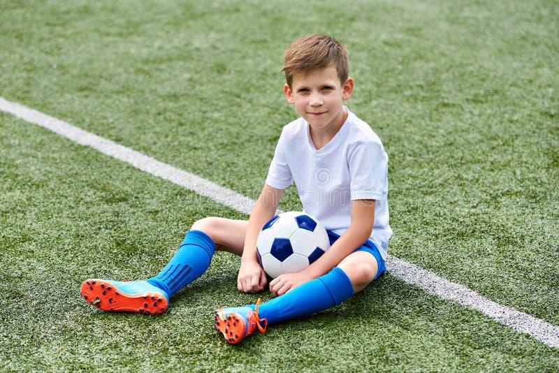 Fútbol del fútbol del muchacho con la bola que se sienta en hierba fotografía de archivo