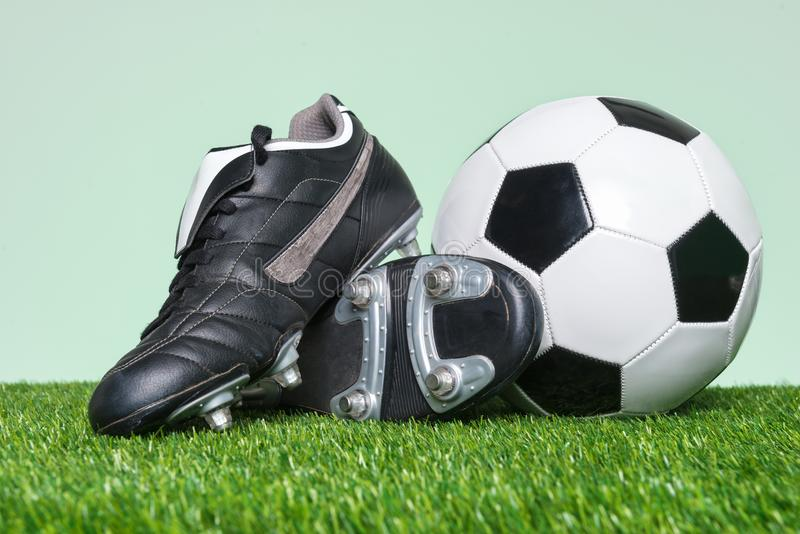 Fútbol o botas y balón de fútbol en hierba fotos de archivo