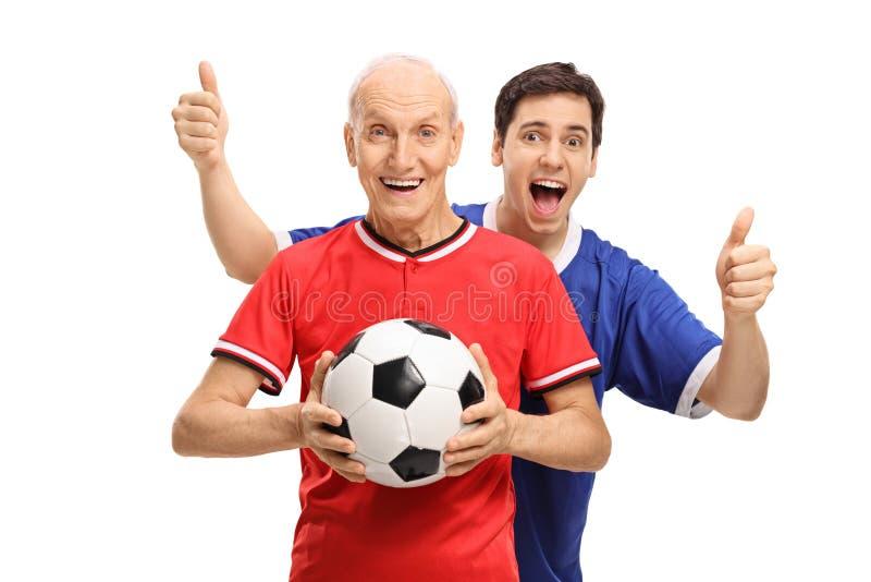 Fútbol que se sostiene mayor con el hombre joven que detiene sus pulgares imagen de archivo