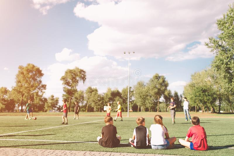 Fútbol Team Playing Match de los niños Partido de fútbol para los niños Jugadores de fútbol jovenes que se sientan en echada Niño imagen de archivo