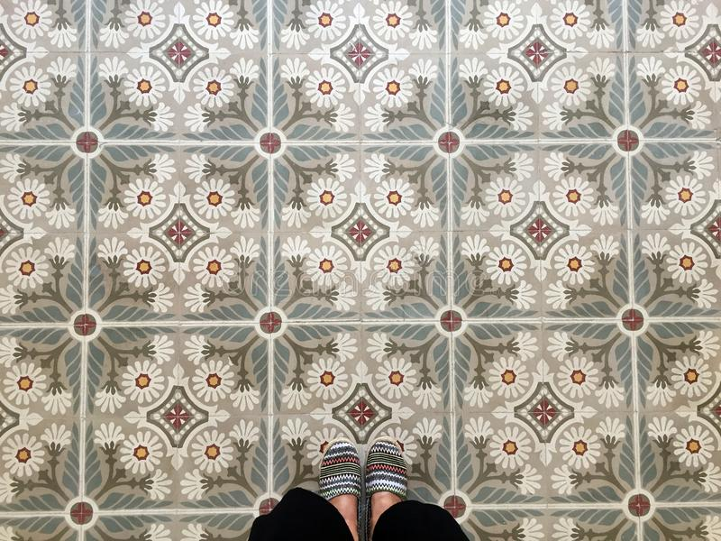 Füße über Weinlesefliesenboden stockbild