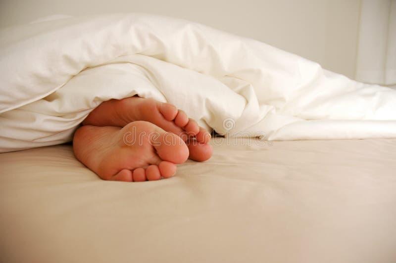 Füße auf Bett lizenzfreie stockfotografie