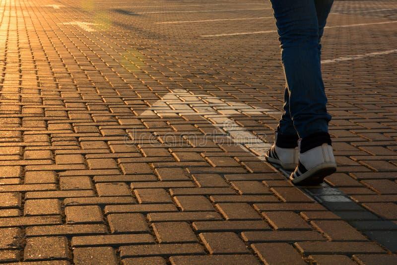 Füße auf dem Straßenpfeil in den Strahlen der untergehenden Sonne stockfoto