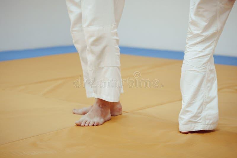 Füße auf dem tatami in der Turnhalle lizenzfreie stockbilder