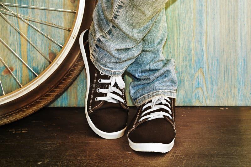 Füße in den Jeans und in den Turnschuhen lizenzfreie stockbilder