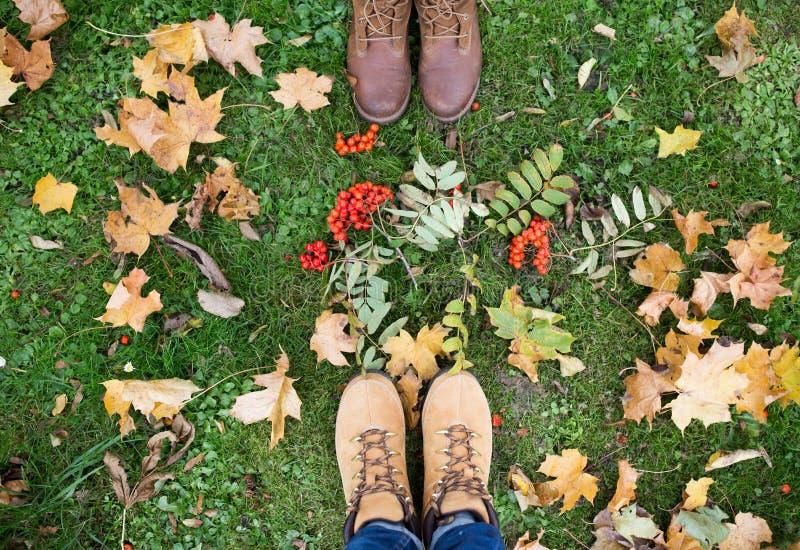 Füße in den Stiefeln mit Vogelbeeren und Herbstlaub lizenzfreie stockbilder