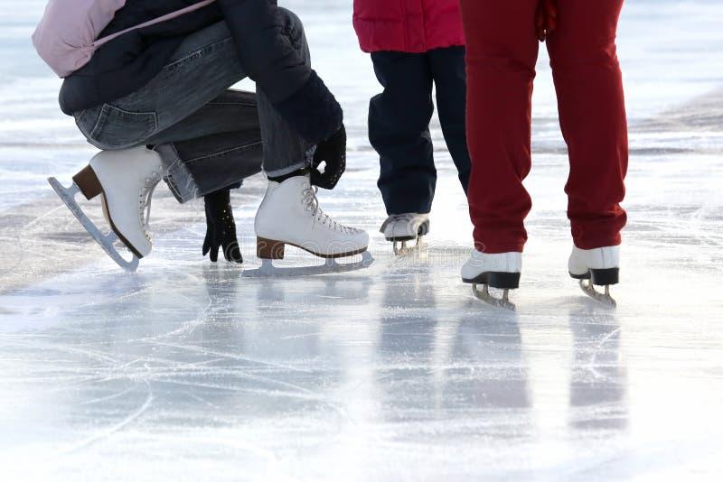 Füße der Leute, die an der Eisbahn eislaufen lizenzfreie stockfotografie