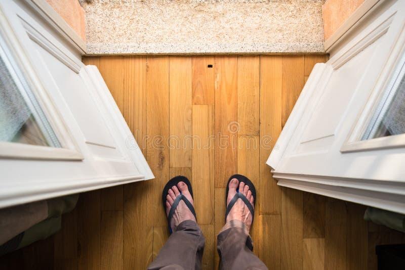 Füße der mittleren gealterten Mannstellung in der Balkontür lizenzfreie stockbilder