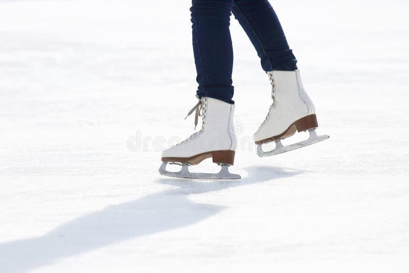 Füße, die auf die Eisbahn eislaufen stockfotografie