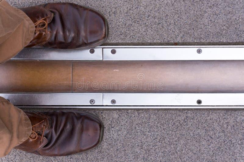 Füße, die auf Gegenseiten des Nullmeridians stehen greenwich lizenzfreie stockbilder