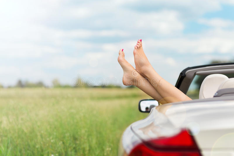 Füße, die aus Kabriolett heraus hängen stockfotografie