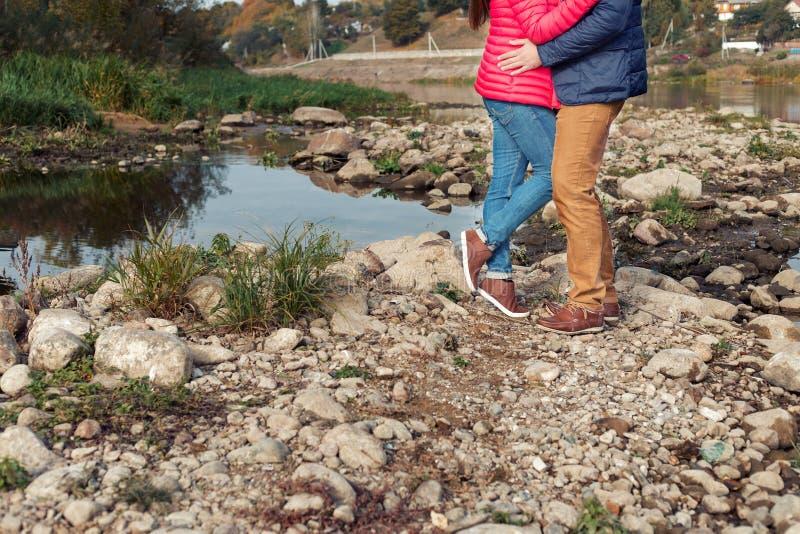 Füße, die glückliches Paar auf dem Ufer des Sees nahe dem Wasser lieben stockfoto