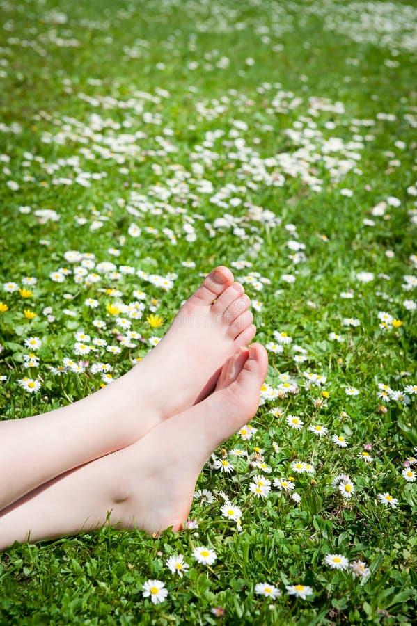 Füße einer jungen Frau, die in einer Wiese liegt lizenzfreies stockbild