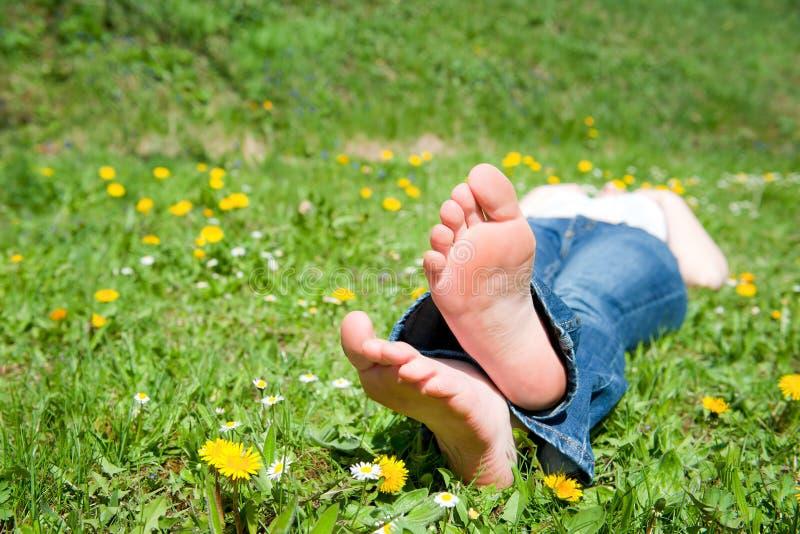 Füße einer jungen Frau, die in einer Wiese liegt stockbilder
