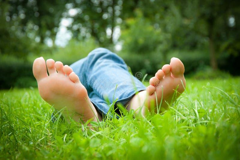 Füße einer jungen Frau, die im Gras liegt stockbilder