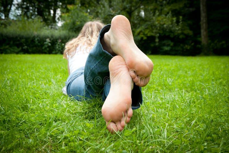 Füße einer jungen Frau, die im Gras liegt stockfotografie