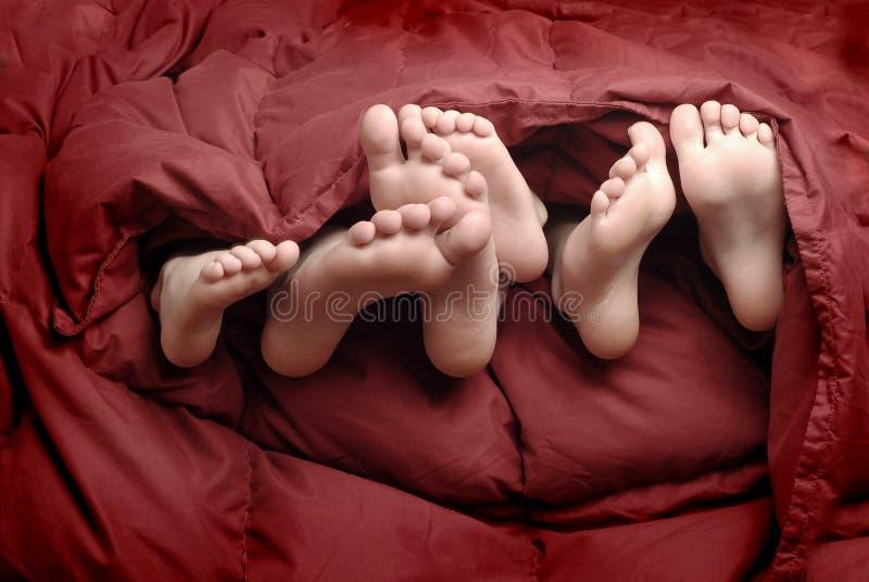 Füße im Bett stockfotos