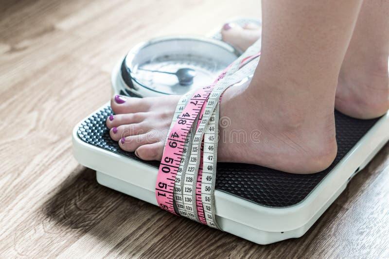 Füße oben gebunden mit messendem Band an einer Gewichtsskala stockbilder