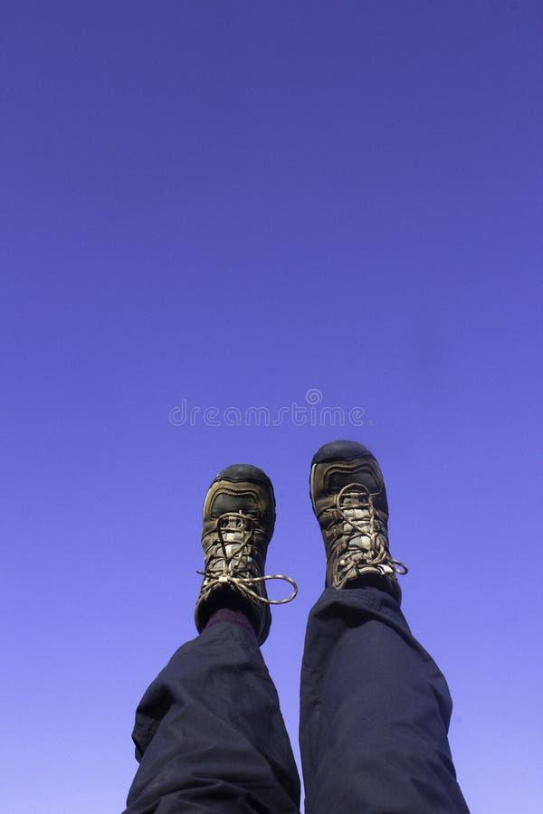 Füße und Beine im braunen Wanderstiefel und in den blauen wandernden Hosen gegen einen klaren blauen Himmel lizenzfreie stockfotografie