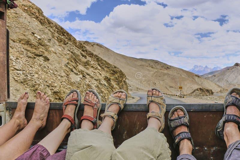 Füße von vier per Anhalter fahrenden Leuten, die auf den beweglichen LKW-Körper in Himalaja-Bergen, Kaschmir, Indien legen lizenzfreie stockbilder