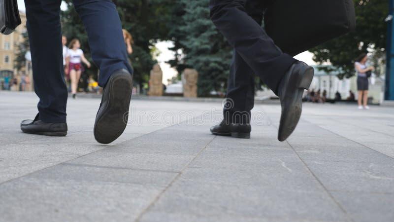 Füße von zwei Geschäftsmännern, die in Stadtstraße gehen Geschäftsleute tauschen aus, um zusammenzuarbeiten Überzeugte Kerle, die stockbilder